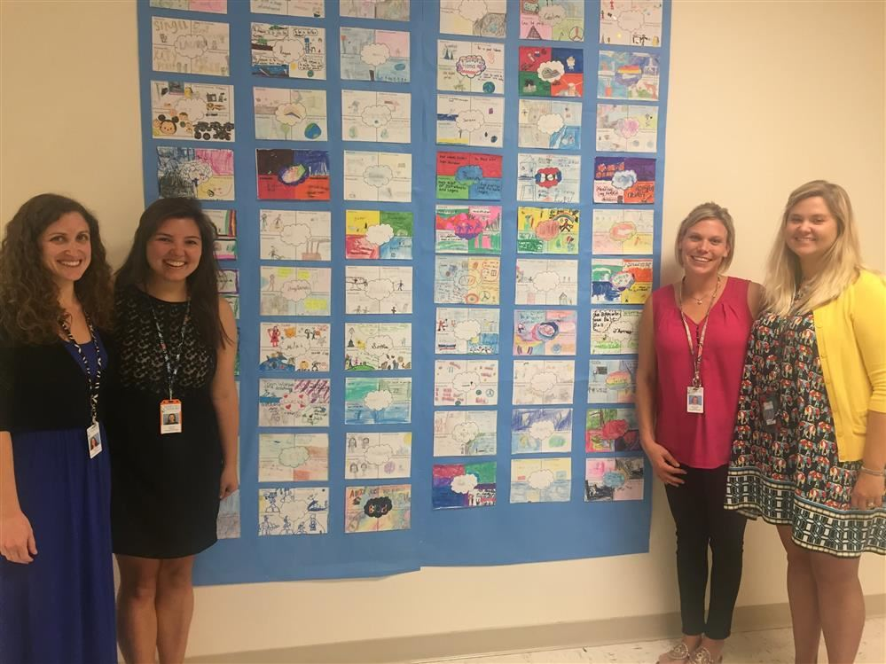 Picture of the four third grade teachers in front of student work